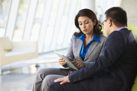 informal clothing: Businesspeople With Digital Tablet Sitting In Modern Office Stock Photo