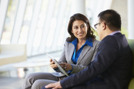business relationship: Businesspeople With Digital Tablet Sitting In Modern Office Stock Photo