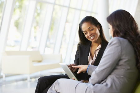 business reception: Businesswomen With Digital Tablet Sitting In Modern Office