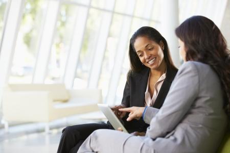 dos personas hablando: Empresarias con la tableta digital Sentado en la oficina moderna