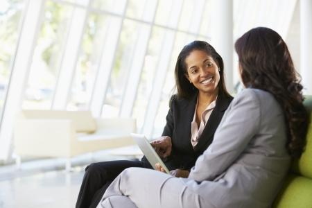 사업: 디지털 태블릿 현대 사무실에 앉아 경제인