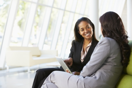 negocios: Empresarias con la tableta digital Sentado en la oficina moderna