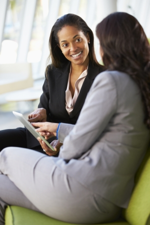 two people talking: Empresarias con la tableta digital Sentado en la oficina moderna