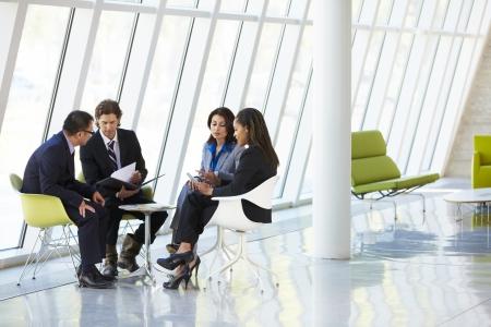 persona sentada: Los empresarios tener la reuni�n en la oficina moderna