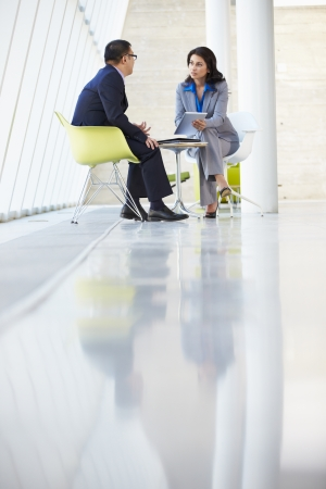 business relationship: Businessman And Businesswoman Meeting In Modern Office Stock Photo