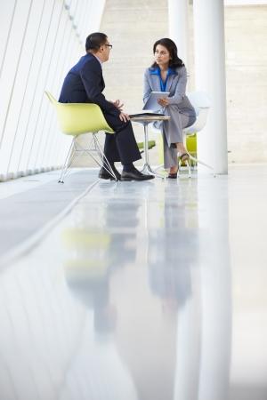 two people talking: Hombre de negocios y empresaria reuni�n en la oficina moderna Foto de archivo
