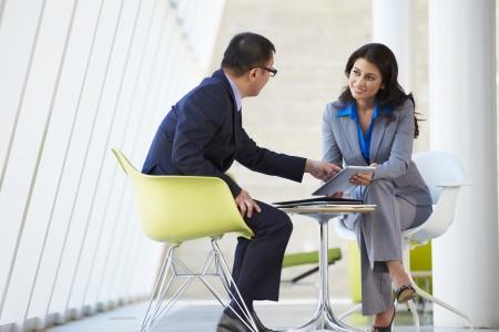 dos personas conversando: Hombre de negocios y empresaria reuni�n en la oficina moderna Foto de archivo