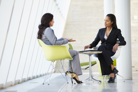two people talking: Two Businesswomen Meeting Around Table In Modern Office Stock Photo