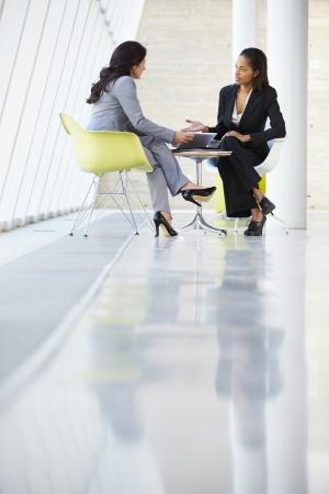 dos personas conversando: Dos empresarias reunión alrededor de la mesa en la oficina moderna