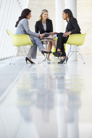business relationship: Three Businesswomen Meeting Around Table In Modern Office