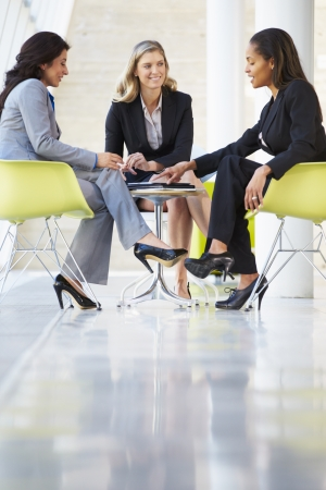 woman in suit: Three Businesswomen Meeting Around Table In Modern Office