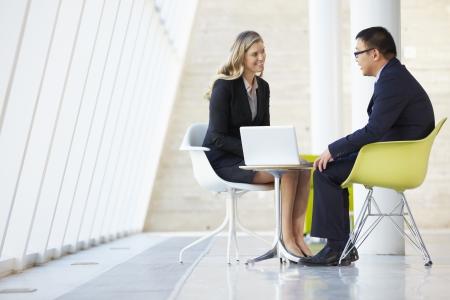 deux personnes qui parlent: R�union d'affaires et femme d'affaires dans le bureau moderne