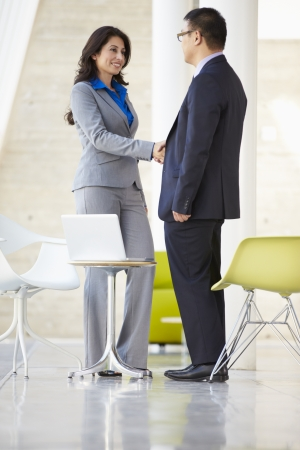 Businessman And Businesswoman Shaking Hands In Modern Office Stock Photo