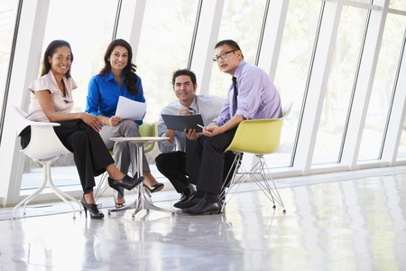 Businesspeople Having Meeting Around Table In Modern Office Stock Photo - 18736791