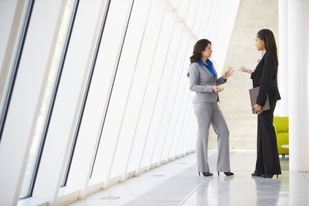 Two Businesswomen Having Informal Meeting In Modern Office photo