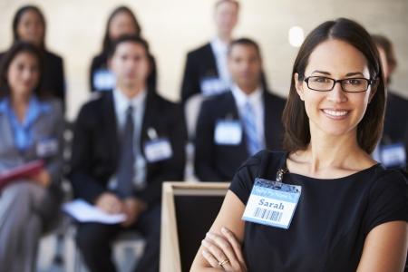 delegates: Businesswoman Delivering Presentation At Conference