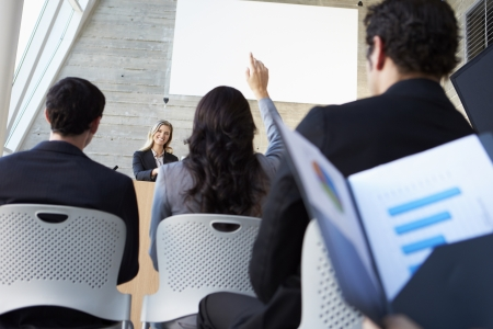large group of business people: Businesswoman Delivering Presentation At Conference