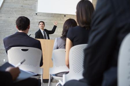 programme: Businessman Delivering Presentation At Conference Stock Photo