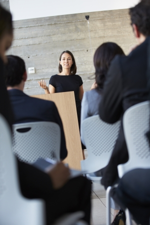 Businesswoman Delivering Presentation At Conference photo