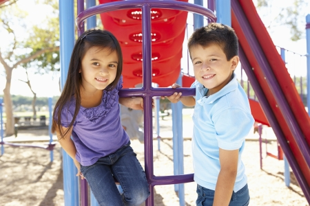 neighbourhood: Boy And Girl On Climbing Frame In Park Stock Photo