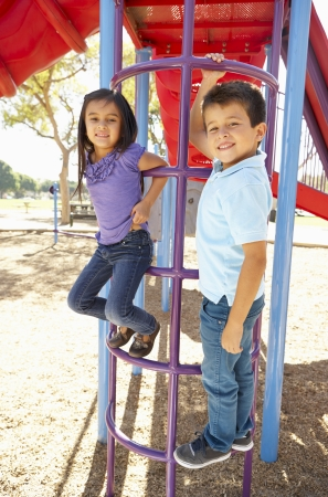 Boy And Girl On Climbing Frame In Park photo