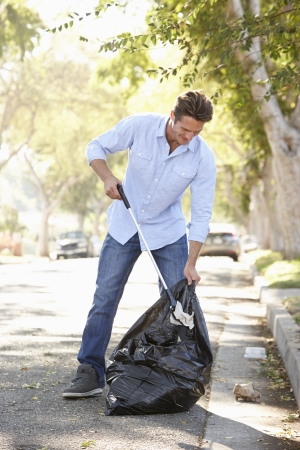 suburban: Man Picking Up Litter In Suburban Street
