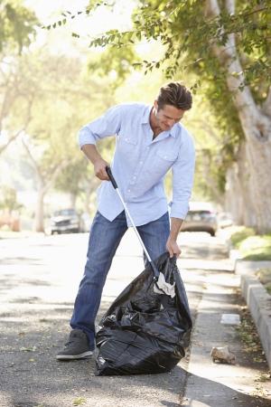 picking up: Man Picking Up Litter In Suburban Street