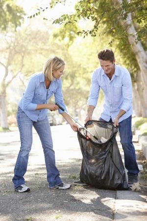 Couple ramasser les ordures dans la banlieue de rue
