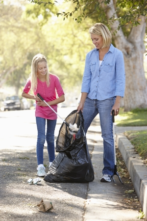 litter: Mother And Daughter Picking Up Litter In Suburban Street