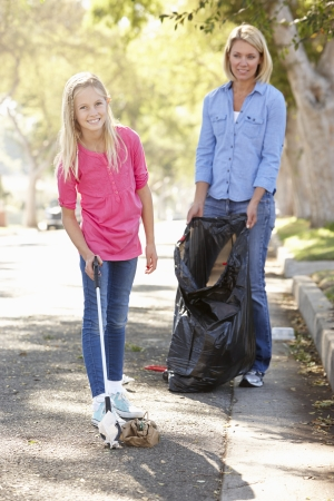 Mother And Daughter Picking Up Litter In Suburban Street photo