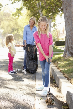 tidying up: Mother And Daughters Picking Up Litter In Suburban Street