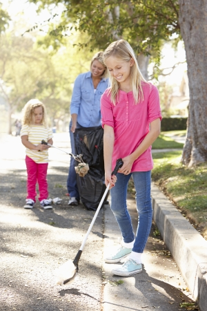 Mother And Daughters Picking Up Litter In Suburban Street photo