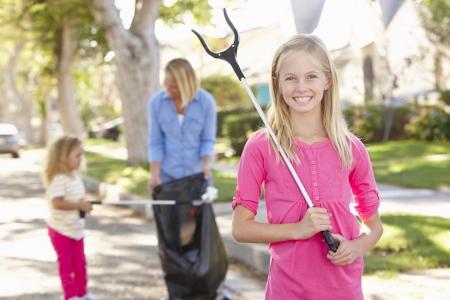 Niños ayudando: Madre e hijas recoger basura en calle suburbana Foto de archivo