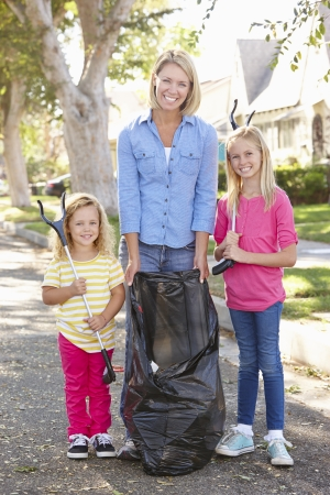 neighbourhood: Mother And Daughters Picking Up Litter In Suburban Street