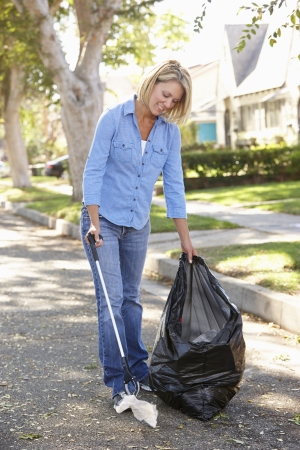 tidying up: Woman Picking Up Litter In Suburban Street Stock Photo