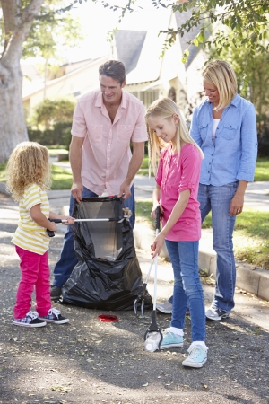 Family Picking Up Litter In Suburban Street photo