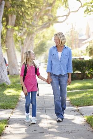 padres e hijos felices: Madre e hija caminando a la escuela en la calle suburbana