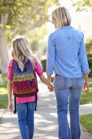 madre con hija: Madre e hija caminando a la escuela en la calle suburbana