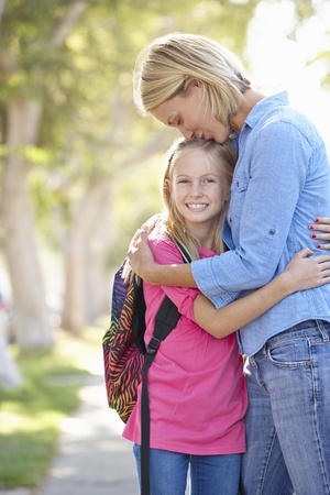 children walking: Mother And Daughter Walking To School On Suburban Street Stock Photo