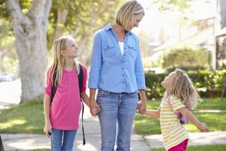 niños caminando: Madre e hijas caminando a la escuela en la calle suburbana