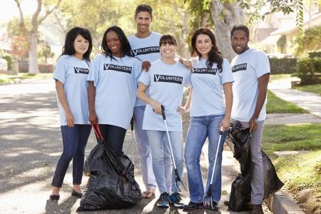 cleaning team: Equipo de voluntarios recogiendo basura en calle suburbana