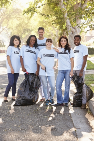 Team Of Volunteers Picking Up Litter In Suburban Street photo