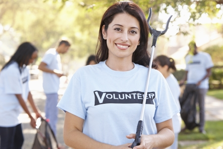 care in the community: Team Of Volunteers Picking Up Litter In Suburban Street