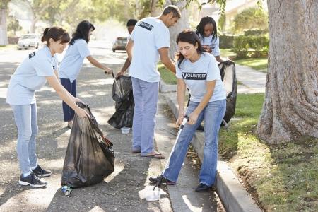 personas ayudando: Equipo de voluntarios recogiendo basura en calle suburbana