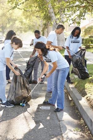 ayudando: Equipo de voluntarios recogiendo basura en calle suburbana