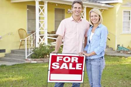 Family Standing By Sold Sign Outside Home Stock Photo