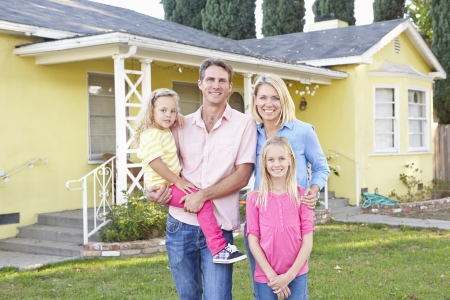 suburban home: Family Standing Outside Suburban Home Stock Photo