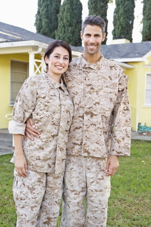 Military Couple In Uniform Standing Outside House photo
