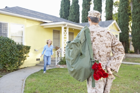 homecoming: Wife Welcoming Husband Home On Army Leave Stock Photo