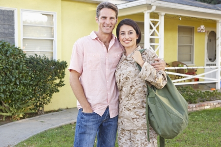 army men: Husband Welcoming Wife Home On Army Leave Stock Photo